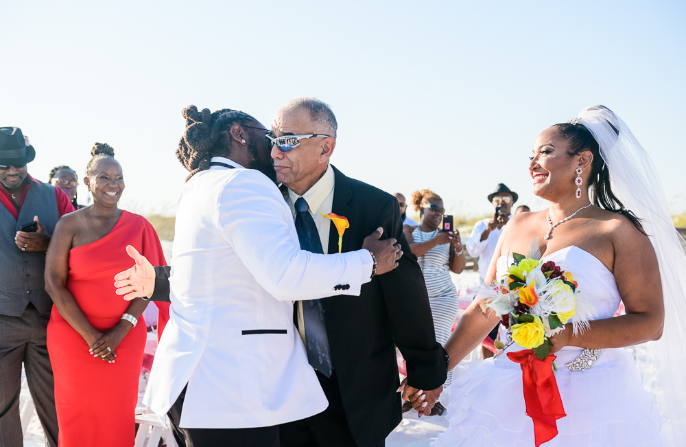 Groom hugging the Father of the Bride when he's giving the Bride away, red and yellow wedding, Royal Red Destination Wedding, Florida wedding photographer, Lazzat Photography
