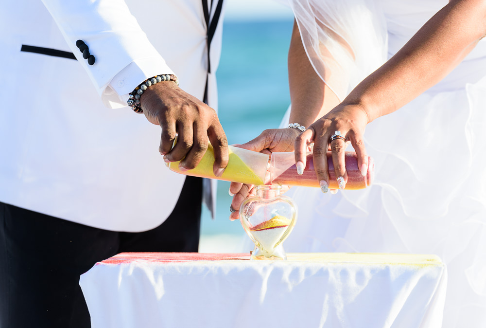 Close up of Bride and Groom doing the unity sand during their ceremony, red and yellow wedding, Royal Red Destination Wedding, Florida wedding photographer, Lazzat Photography