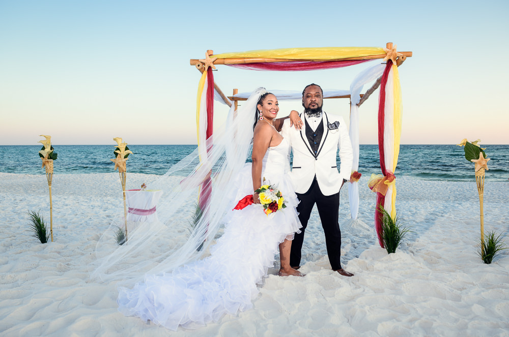 Bride and Groom in front of their red and yellow wedding arch on the beach, high low wedding dress, Royal Red Destination Wedding, Florida wedding photographer, Lazzat Photography