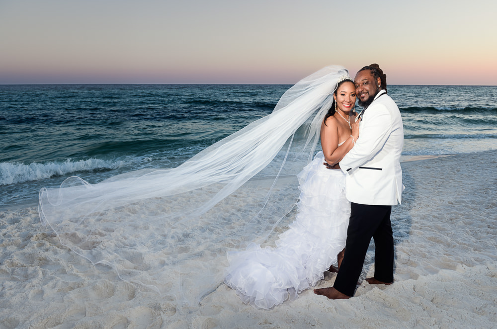 Bride and Groom smiling on the beach at sunset, high low wedding dress, Royal Red Destination Wedding, Florida wedding photographer, Lazzat Photography