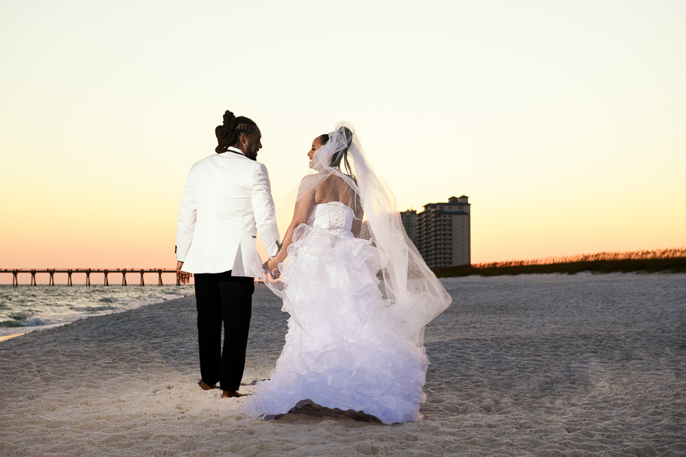 Bride and Groom walking down the beach at sunset, high low wedding dress, Royal Red Destination Wedding, Florida wedding photographer, Lazzat Photography
