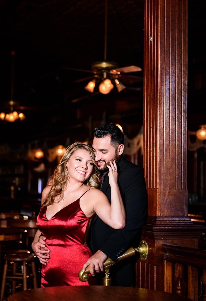 Couple hugging in Seville Quarter, New Orleans Inspired Engagement Session, Long red gown, Pensacola engagement photographer, Lazzat Photography