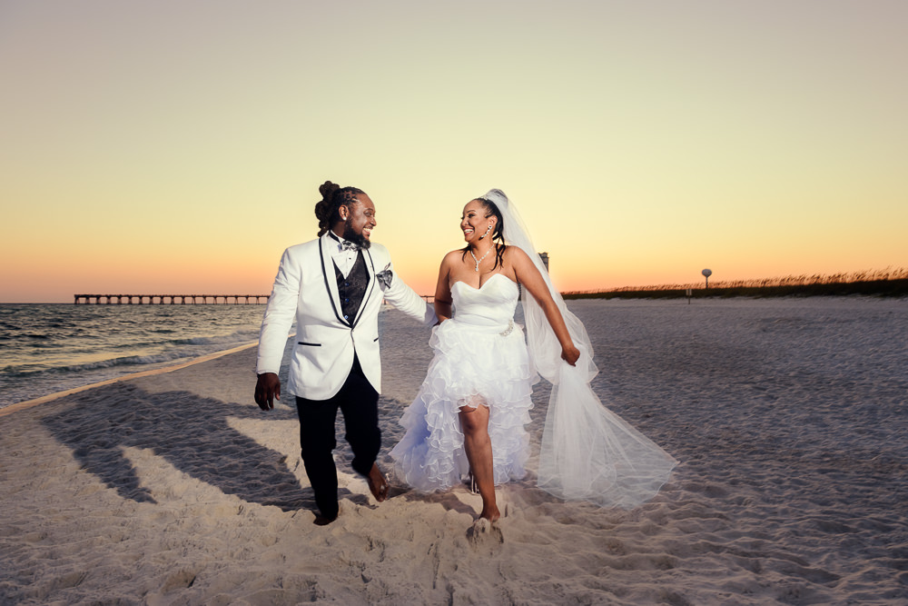 Bride and Groom walking on the beach at sunset, high low wedding dress, Royal Red Destination Wedding, Florida wedding photographer, Lazzat Photography