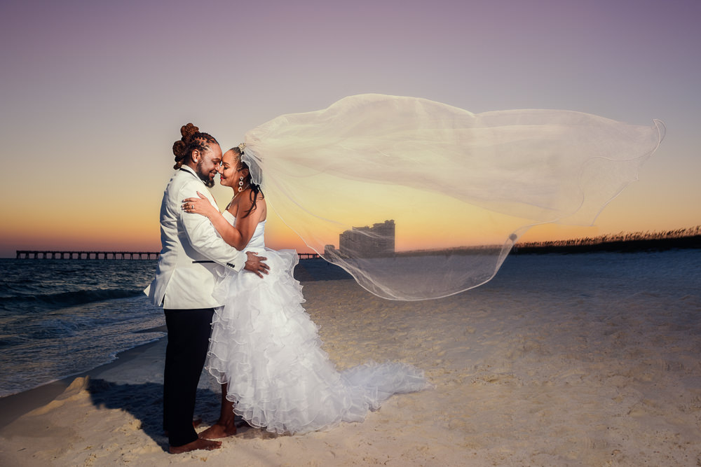 Bride and Groom hugging with veil flying on the beach at sunset, Royal Red Destination Wedding, Florida wedding photographer, Lazzat Photography