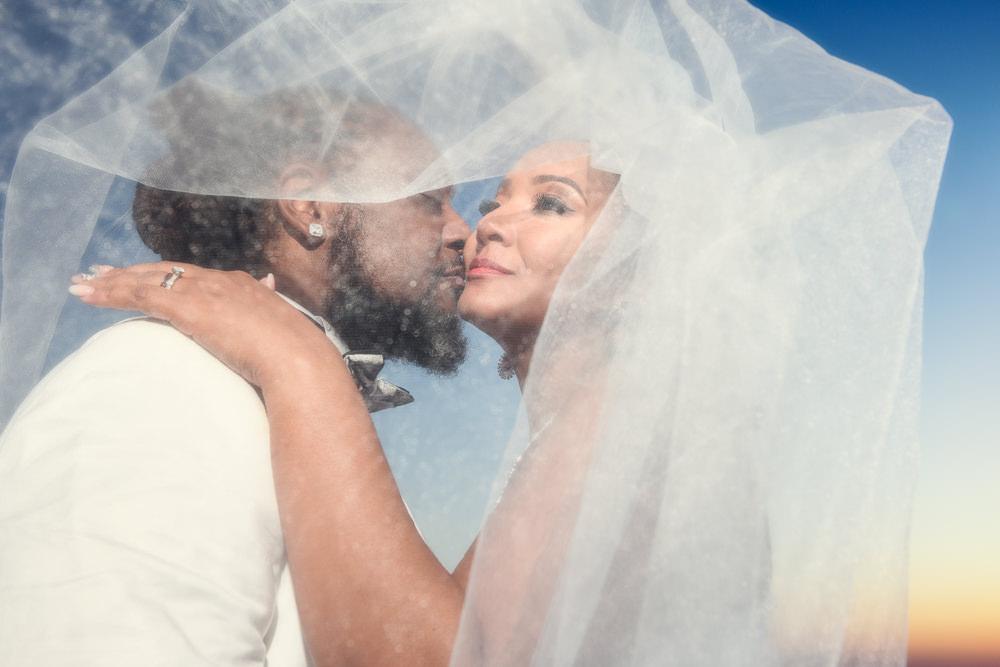 Groom kissing Bride's cheek under the veil on the beach at sunset, Royal Red Destination Wedding, Florida wedding photographer, Lazzat Photography