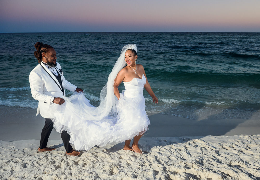Groom carrying his Bride's wedding dress as they walk along the beach, Royal Red Destination Wedding, Florida wedding photographer, Lazzat Photography