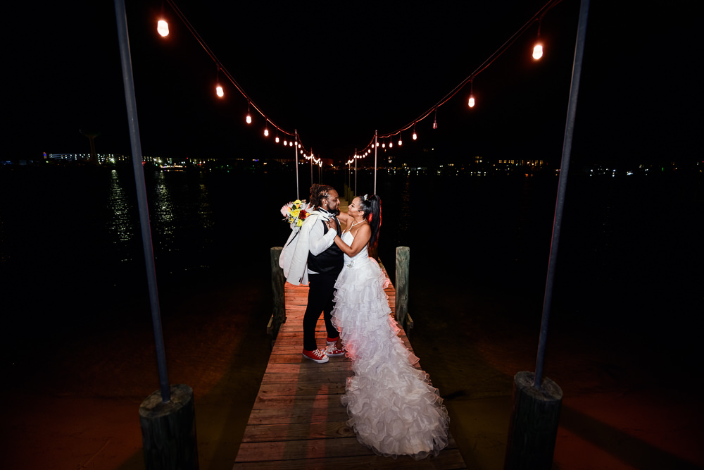 Bride and Groom looking at each other on the pier at night with twinkle lights, Royal Red Destination Wedding, Florida wedding photographer, Lazzat Photography