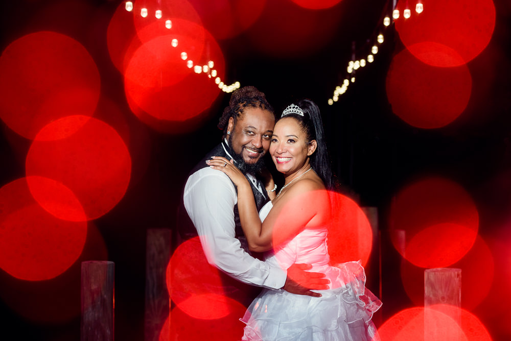 Bride and Groom smiling at night with red and white twinkle lights, Royal Red Destination Wedding, Florida wedding photographer, Lazzat Photography
