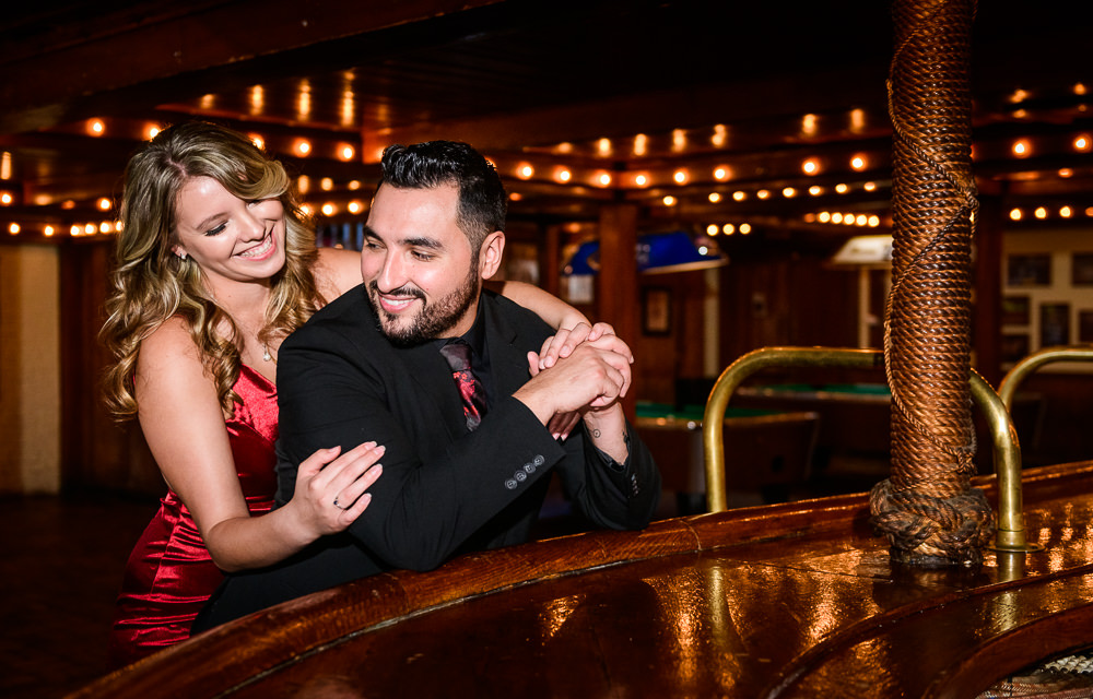 Couple smiling at each other in Seville Quarter, New Orleans Inspired Engagement Session, Long red gown, Pensacola engagement photographer, Lazzat Photography
