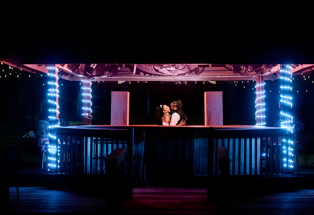 Bride and Groom kissing in the tiki bar at night, Royal Red Destination Wedding, Florida wedding photographer, Lazzat Photography