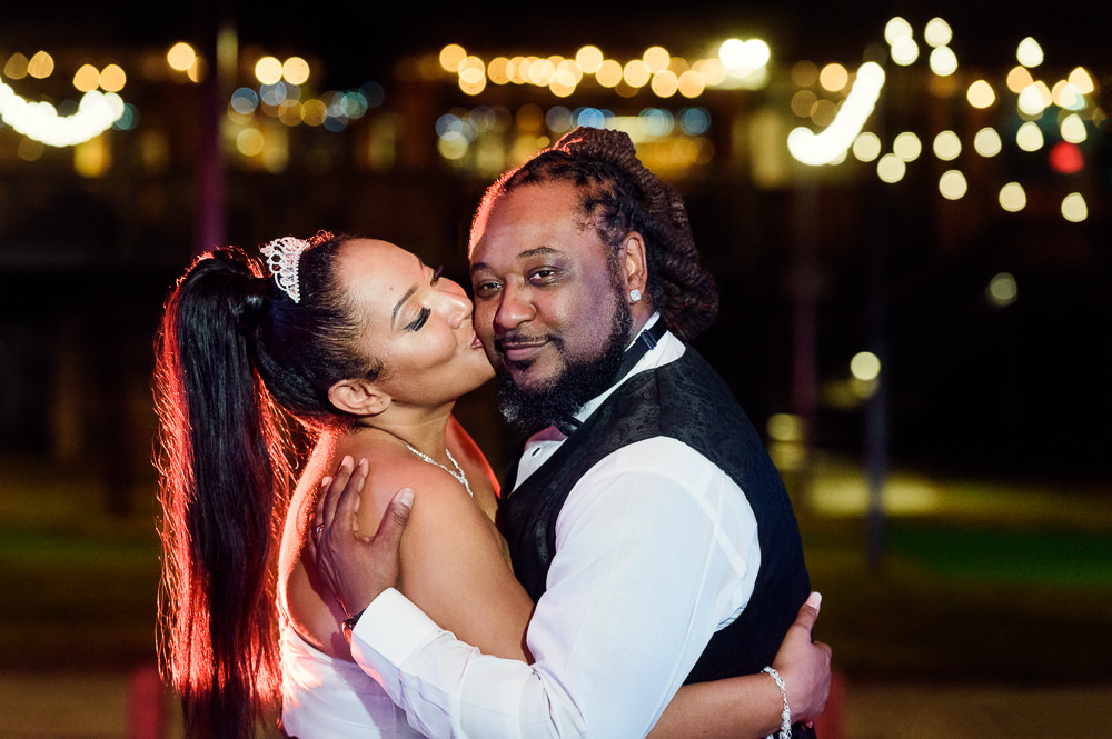 Bride kissing Groom at night with twinkle lights, Royal Red Destination Wedding, Florida wedding photographer, Lazzat Photography