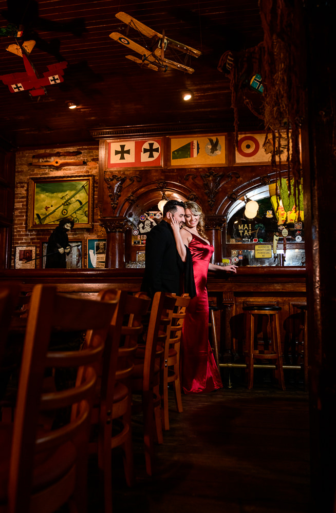 Couple standing under model airplane at Seville Quarter, New Orleans Inspired Engagement Session, Long red gown, Pensacola engagement photographer, Lazzat Photography