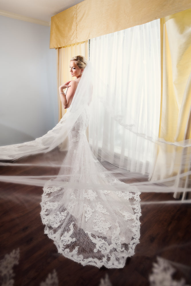 Bride looking over her shoulder with her long lace veil flying, lace wedding dress, bridal portrait, Skopelos at New World, Palafox Wharf Pensacola Wedding, Orlando Florida Wedding photographer, Lazzat Photography