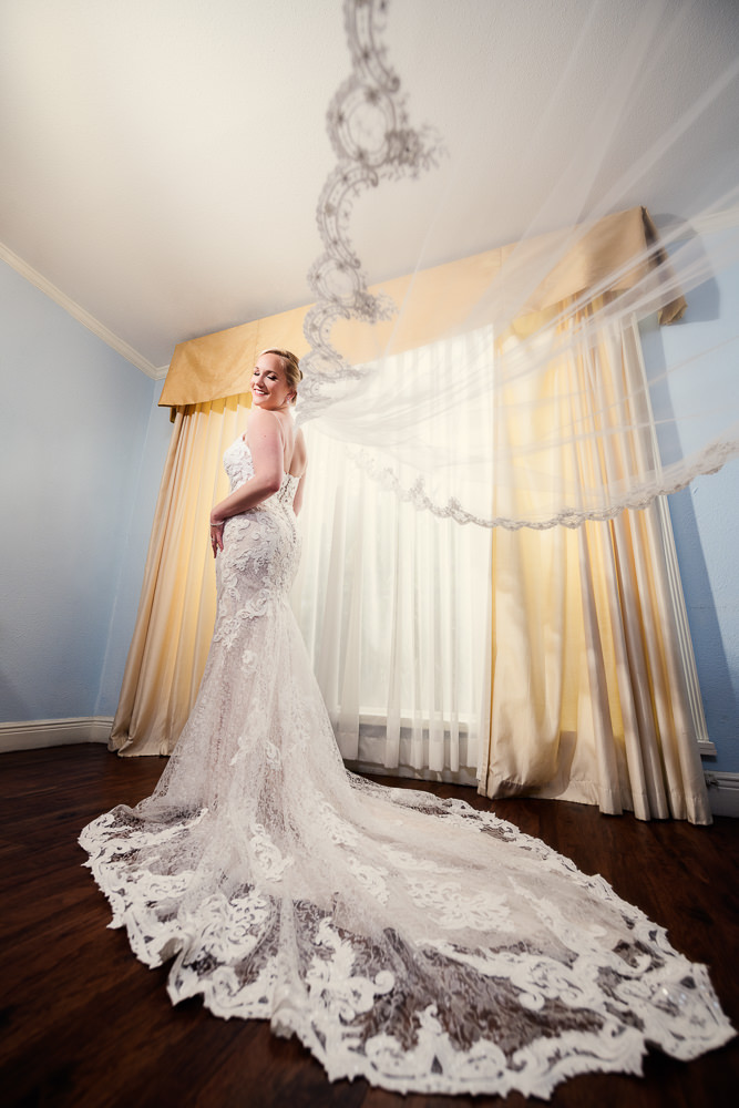 Bride smiling over her shoulder with her long lace veil flying, lace wedding dress, bridal portrait, Skopelos at New World, Palafox Wharf Pensacola Wedding, Orlando Florida Wedding photographer, Lazzat Photography