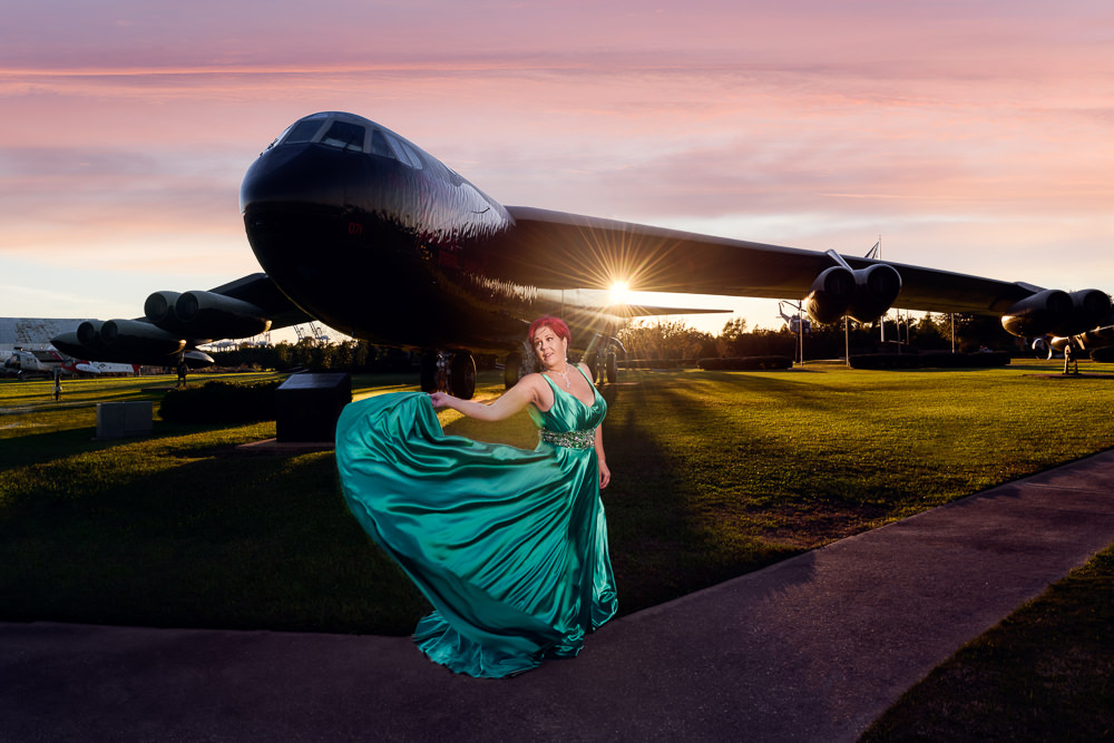 Women twirling her dress in front of a Coast Guard plane, green formal gown, pink hair, EPIC couple shoot, Lazzat Photography
