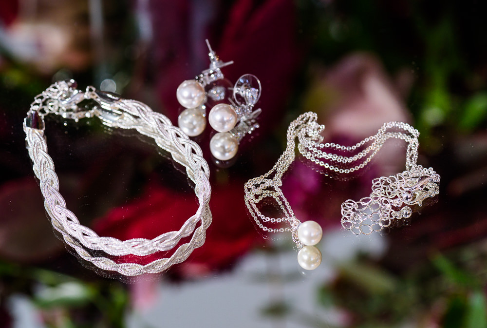 Bride's details on a mirrored table, pearl earrings, pearl necklace, braided bracelet, Skopelos at New World, Palafox Wharf Pensacola Wedding, Orlando Florida Wedding photographer, Lazzat Photography