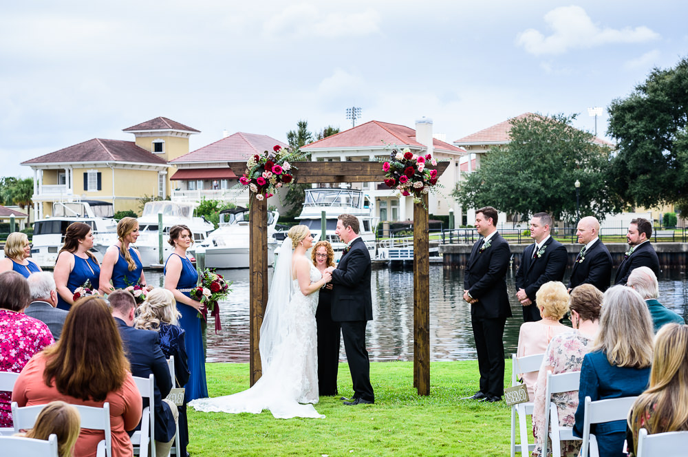 Bride and Groom under their wedding arch during their waterfront wedding ceremony, Palafox Wharf waterfront, Palafox Wharf Pensacola Wedding, Orlando Florida Wedding photographer, Lazzat Photography