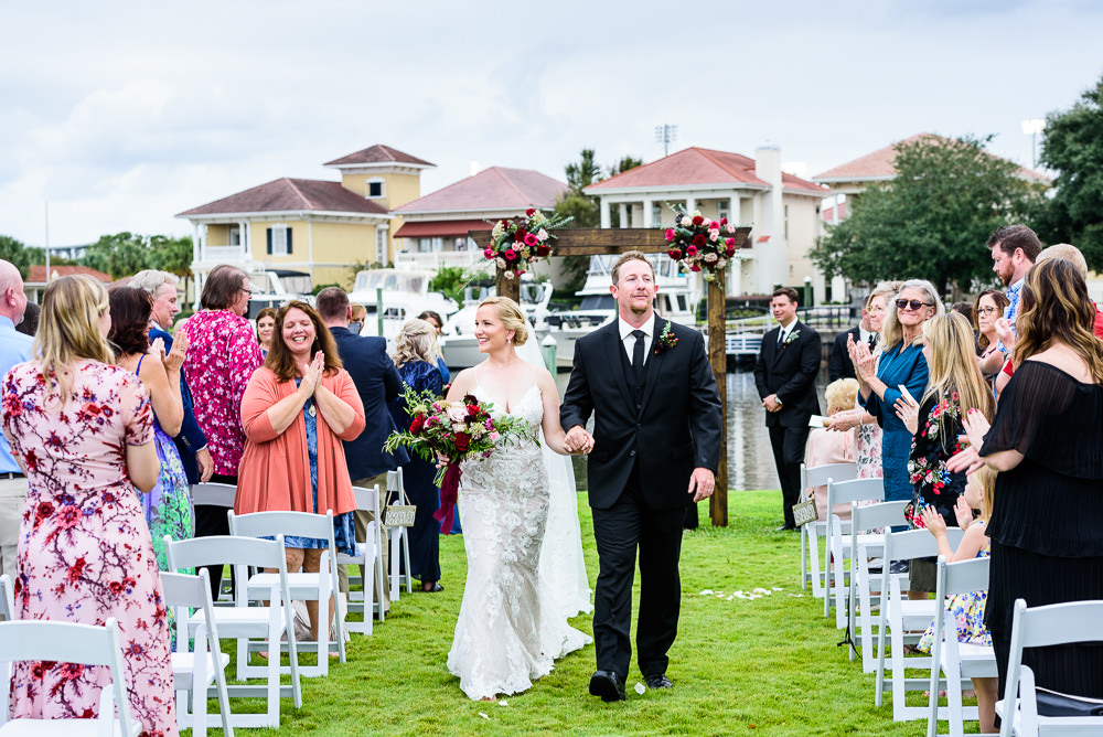 Bride and Groom walking up the aisle, long lace veil, lace wedding dress, Palafox Wharf waterfront, Palafox Wharf Pensacola Wedding, Orlando Florida Wedding photographer, Lazzat Photography