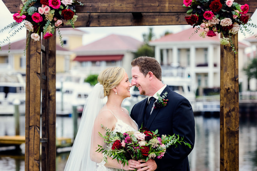 Bride and Groom smiling at each other in front of wedding arch, Palafox Wharf waterfront, Palafox Wharf Pensacola Wedding, Orlando Florida Wedding photographer, Lazzat Photography