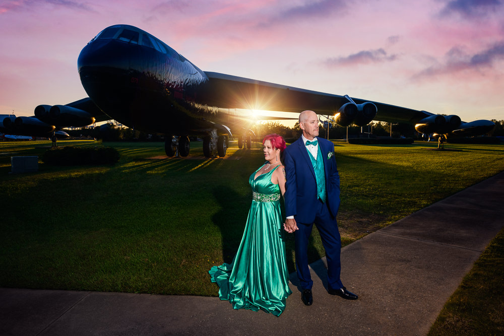 Couple leaning on each other in front of a Coast Guard plane, green formal gown, pink hair, EPIC couple shoot, Lazzat Photography