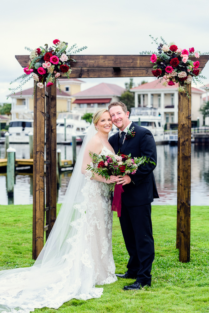 Bride and Groom in front of wedding arch, long lace veil, lace wedding dress, Palafox Wharf waterfront, Palafox Wharf Pensacola Wedding, Orlando Florida Wedding photographer, Lazzat Photography