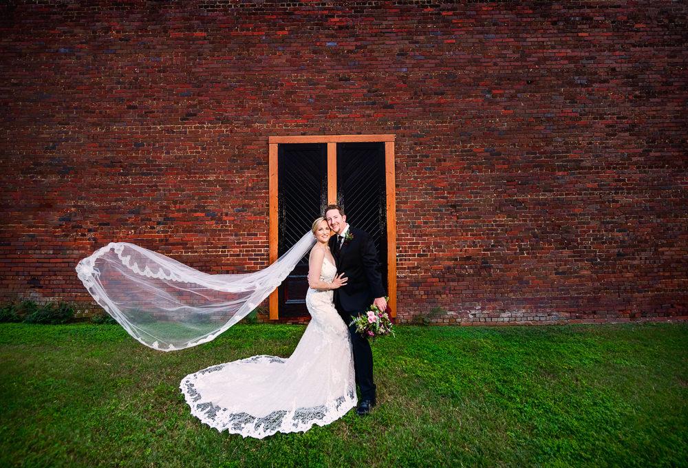 Bride and Groom smiling with long lace veil flying, lace wedding dress, Palafox Wharf waterfront, Palafox Wharf Pensacola Wedding, Orlando Florida Wedding photographer, Lazzat Photography