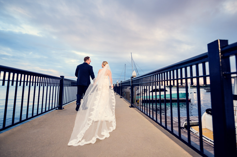 Bride and Groom walking down Palafox Pier, lace wedding dress, long lace veil, Palafox Wharf Pensacola Wedding, Orlando Florida Wedding photographer, Lazzat Photography