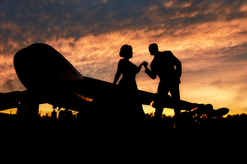 Silhouette of couple next to a Coast Guard plane, green formal gown, pink hair, EPIC couple shoot, Lazzat Photography
