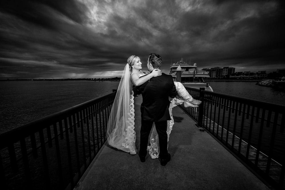 Groom carrying his Bride on Palafox pier, Black and white, Palafox Wharf Pensacola Wedding, Orlando Florida Wedding photographer, Lazzat Photography