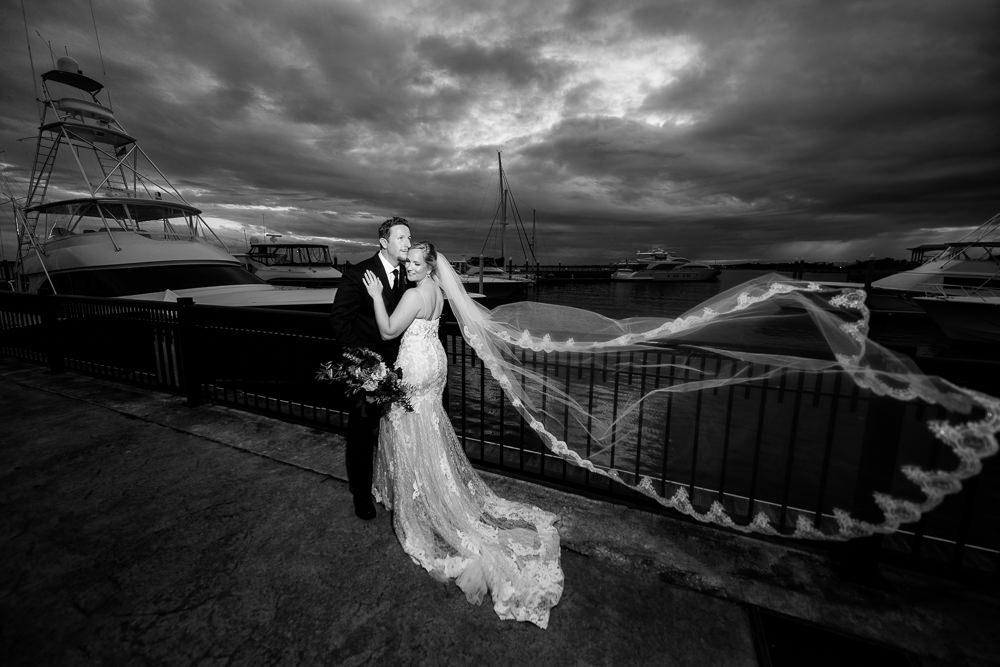 Bride and Groom at Palafox pier with veil flying, black and white, Palafox Wharf Pensacola Wedding, Orlando Florida Wedding photographer, Lazzat Photography