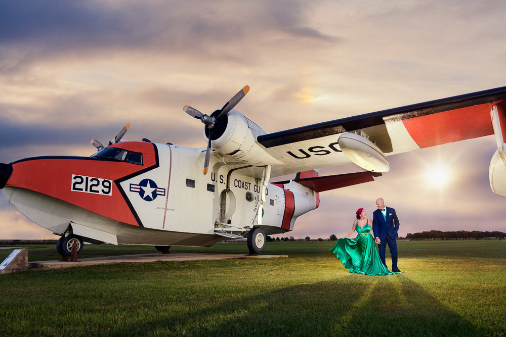 Couple next to a Coast Guard plane, green formal gown, pink hair, EPIC couple shoot, Lazzat Photography