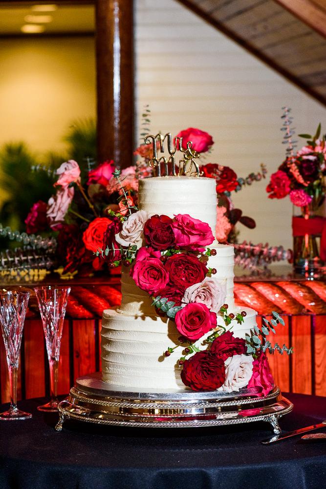 White wedding cake with pink and red flowers and Mr & Mrs wedding cake topper, Palafox Wharf Pensacola Wedding, Orlando Florida Wedding photographer, Lazzat Photography