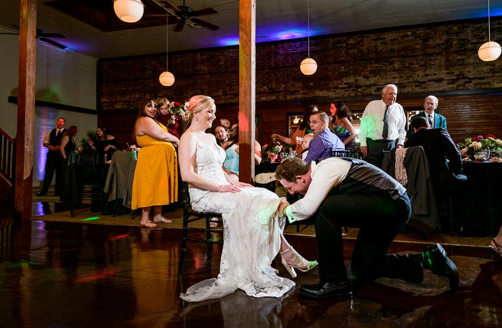 Groom taking off Bride's garter, Palafox Wharf Pensacola Wedding, Orlando Florida Wedding photographer, Lazzat Photography