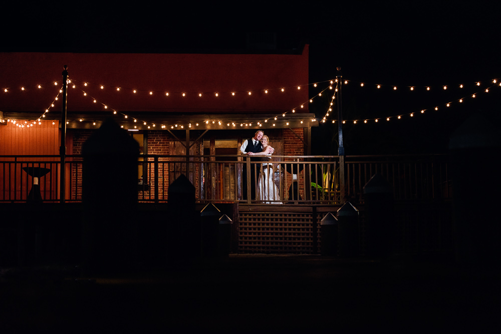 Bride and Groom outside of Palafox Wharf waterfront at night with bistro lights, Palafox Wharf Pensacola Wedding, Orlando Florida Wedding photographer, Lazzat Photography