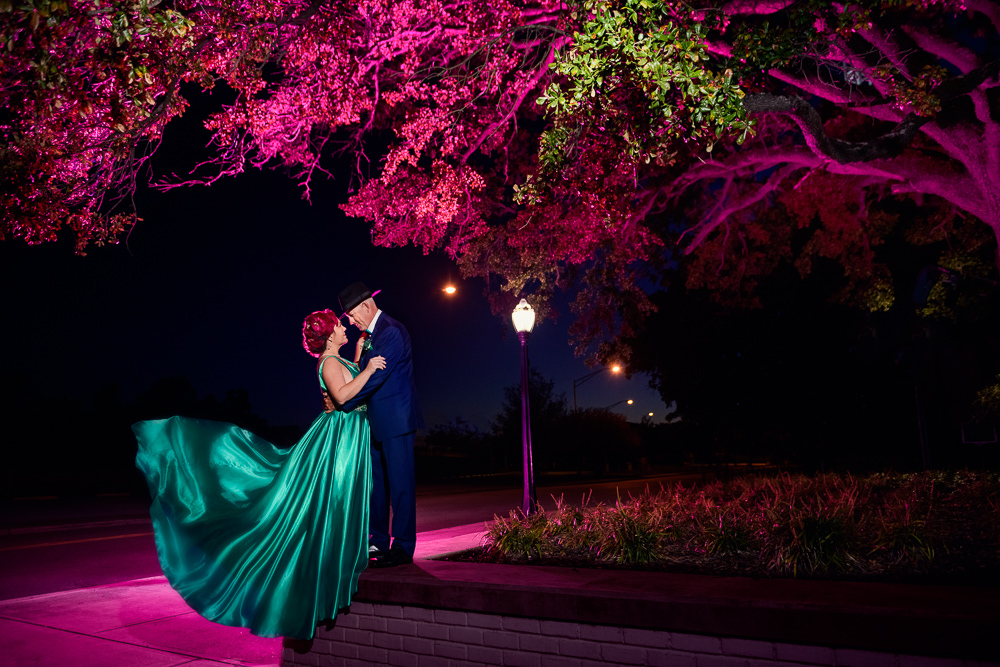 Couple standing on ledge, pink and green lighting, green formal gown, pink hair, EPIC couple shoot, Lazzat Photography