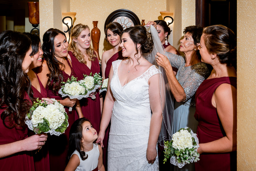 Bride surrounded by her Bridesmaids and daughter while her mother places her veil, burgundy bridesmaids dresses, lace wedding dress, multicultural filipino wedding, Catholic country club wedding, Pensacola Florida, Lazzat Photography