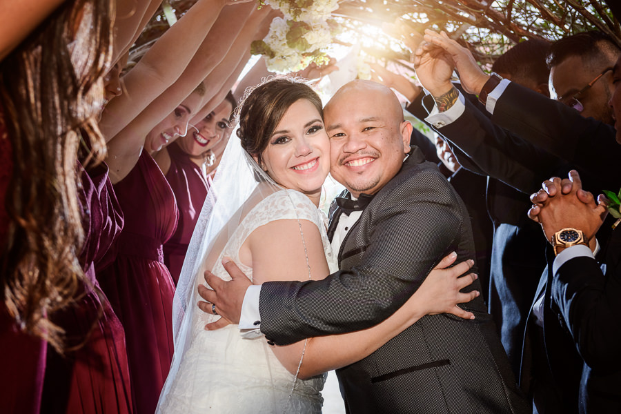 Bride and Groom smiling under the vine-covered arch with their wedding party, multicultural filipino wedding, Catholic country club wedding, Pensacola Florida, Lazzat Photography