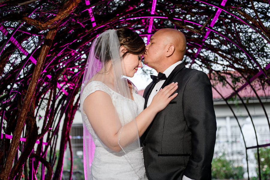 Groom kissing his Bride on the head under pink lit vine-covered arch, multicultural filipino wedding, Catholic country club wedding, Pensacola Florida, Lazzat Photography