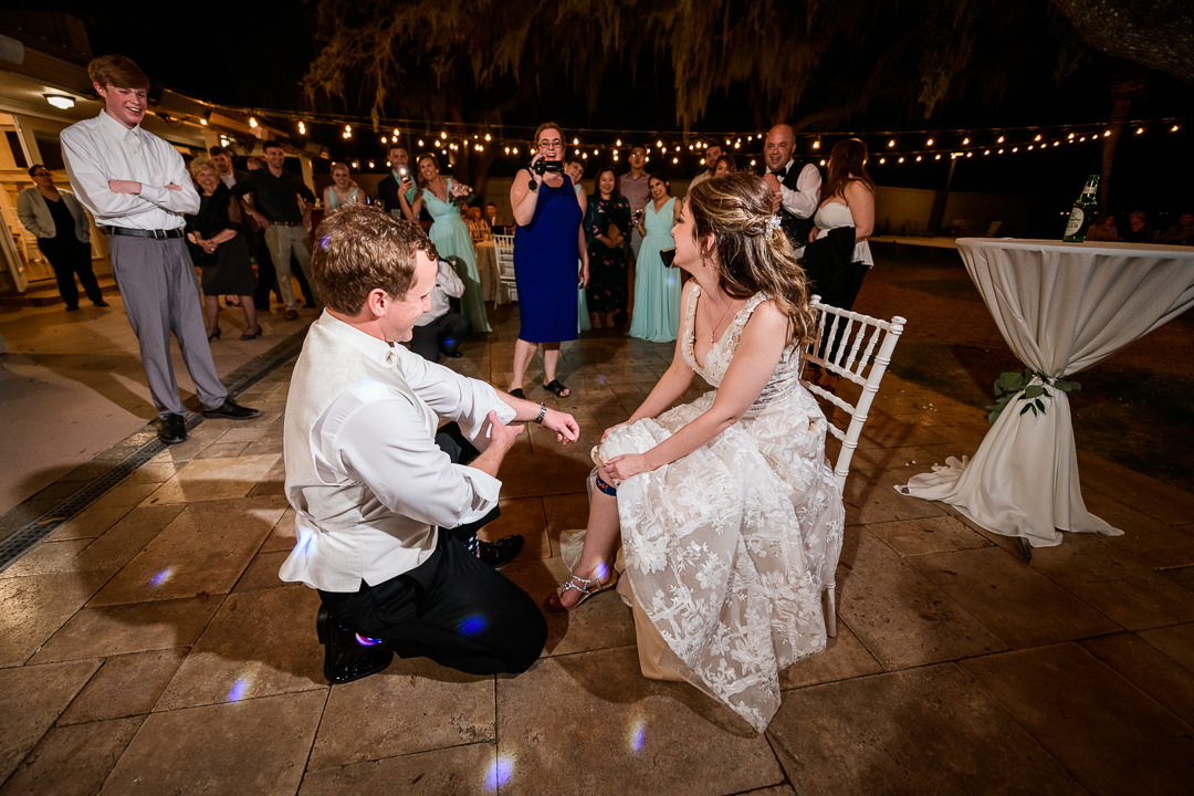 Groom taking off the Bride's garter, lace wedding dress, Destin Bay House Wedding, Destin Florida, Lazzat Photography, Florida wedding photographer, Orlando wedding photographer