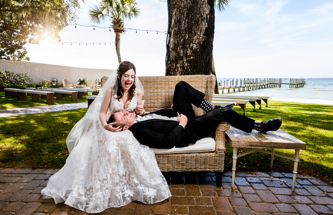 Groom laying on the Bride's lap laughing on a bench outside the Destin Bay House Wedding, Destin Florida, Lazzat Photography, Florida wedding photographer, Orlando wedding photographer