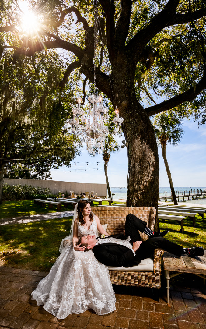 Groom laying on the Bride's lap on a bench outside the Destin Bay House Wedding, Destin Florida, Lazzat Photography, Florida wedding photographer, Orlando wedding photographer