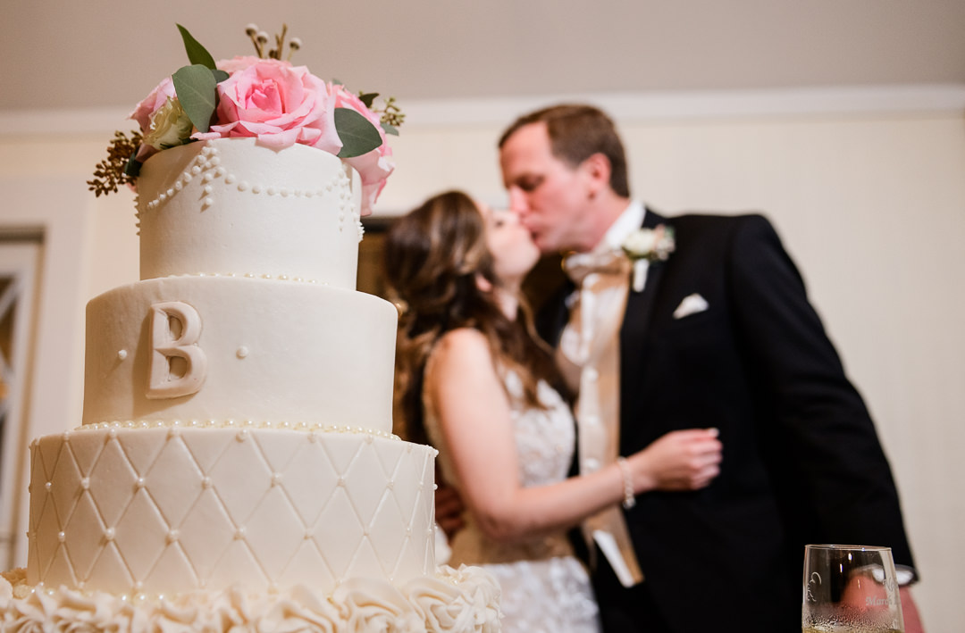 Bride and Groom kissing behind their wedding cake, Destin Bay House Wedding, Destin Florida, Lazzat Photography, Florida wedding photographer, Orlando wedding photographer